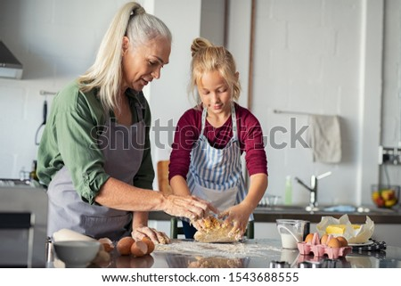 Lovely grandmother and granddaughter kneading dough on counter kitchen. Little cute girl prepare the dough from flour with granny. Happy mature granny and child wearing apron preparing recipe for pie.
