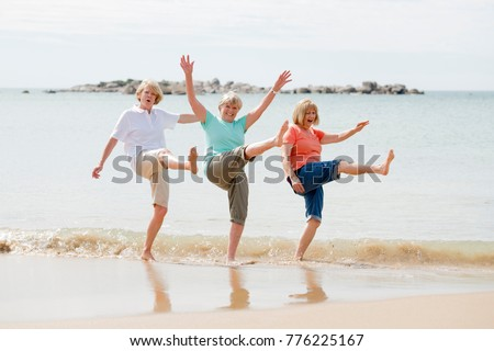 lovely group of three senior mature retired women on their 60s having fun enjoying together happy walking on the beach smiling playful in female friendship and girlfriends on holidays concept