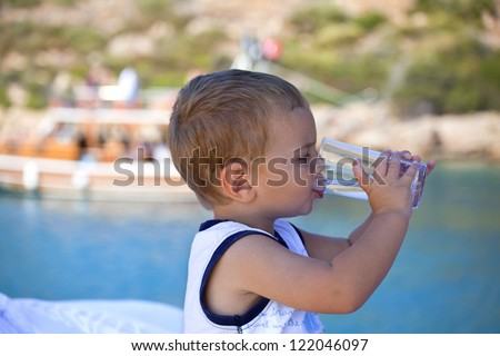 lovely handsome boy is drinking water on a boat
