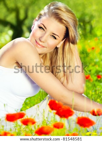 Lovely happy female closeup portrait, sitting in the poppy flower field, enjoying nature, summertime leisure concept