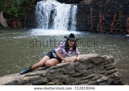 Lovely Hispanic cowgirl in black cowboy hat, blue jean shorts and a big belt buckle reclining on a stone before a pool of water and a waterfall