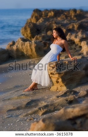 lovely hispanic lady rests on coral rock along beach in florida