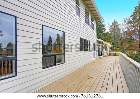 Lovely home features a wraparound deck lined with a wooden handrails overlooking the backyard.  #761312761