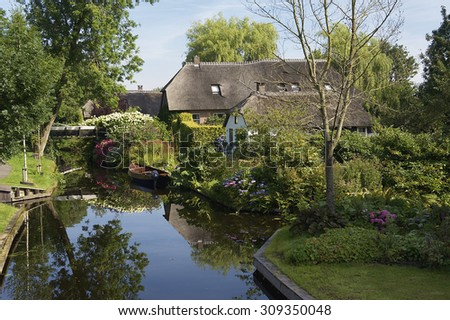 Lovely houses in the village Giethoorn with a boat in the canal. There is no car traffic; only boats.
