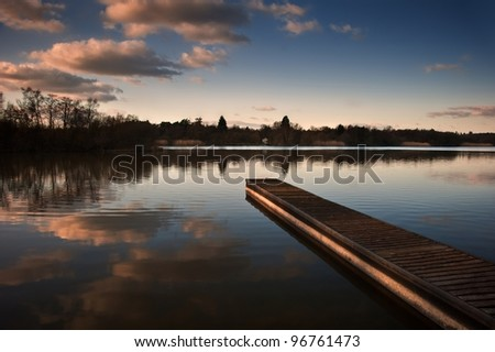 Lovely image of late sunset sky over calm lake landscape with long fishing jetty pier and vibrant colors