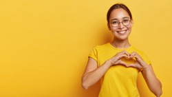 Lovely korean woman with happy smile, shapes heart with both hands, expresses love to you, wears round spectacles and yellow t shirt, says be my valentine flirts with boyfriend poses indoor copy space