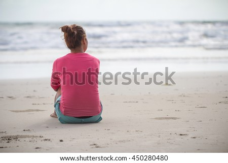 Lovely lady sitting alone on the sand. lonely lovelorn women sit on the beach.Style loneliness.divorce.Let's Stay Together