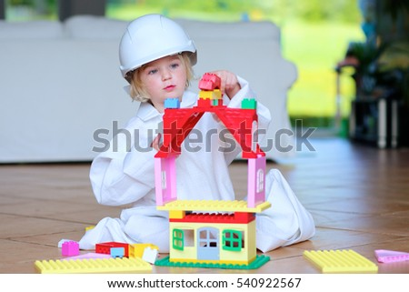 Lovely laughing little child, preschool age toddler girl wearing safety helmet playing indoors building house with colorful blocks sitting on a floor in big playroom at home or kindergarten #540922567
