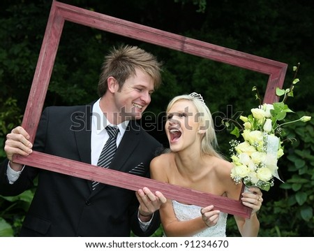 Lovely laughing wedding couple looking through a wooden picture frame