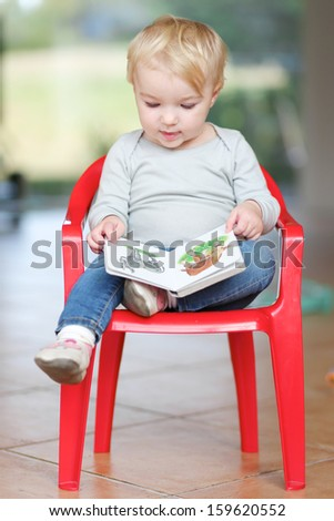 Lovely little baby girl sitting indoors on a small red plastic chair reading children book about animals