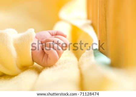 Lovely little clenched hand, infant hand in baby bed with wooden fence.