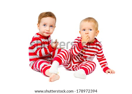 Lovely little fellows in Christmas costumes eat sweets isolated on white background
