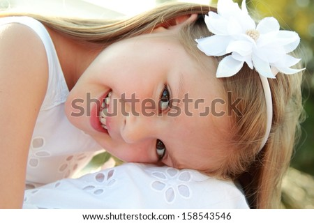Lovely little girl in white dress sitting on parapet near the fountain in the summer hottest day/Portrait of beautiful girl near the fountain