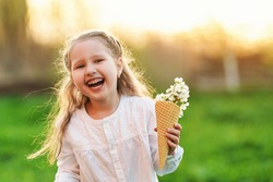 lovely little girl is laughing and holding the tree's spring flowers in a waffle cone in her hand. The concept is the beginning of a new, spring mood and childlike spontaneity. Warm sunset.
