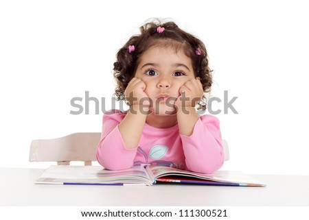 Lovely little girl is reading sitting at the table