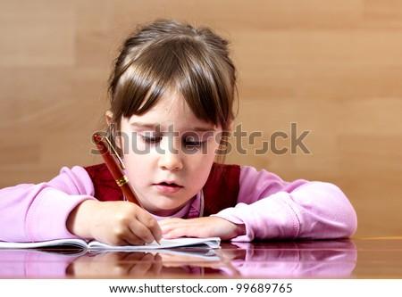Lovely little girl learning to write