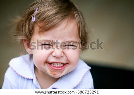 Stock Photo Lovely little girl making funny face after eating chocolate