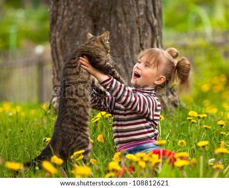 Lovely little girl playing with a cat.