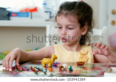 Lovely little girl playing with plasticine in her room