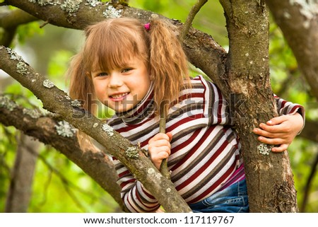 Lovely little girl posing sitting on a tree in the garden