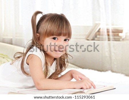 Lovely little girl reading a book on bed