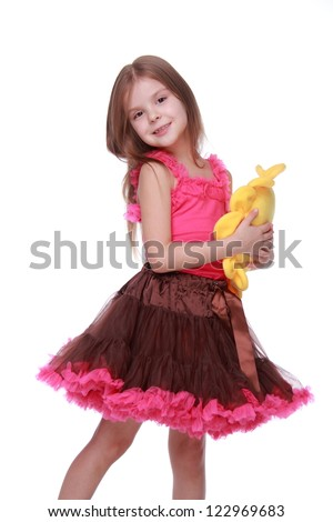 Lovely little girl wearing bright clothes with toy of sun symbol isolated on white