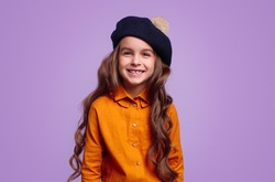 Lovely little girl with long wavy hair wearing colorful shirt and beret smiling brightly and looking at camera against violet background