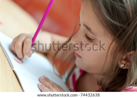 Lovely little girl working in her school project at home