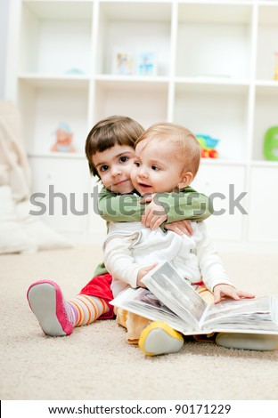 stock photo : Lovely little sister hugging her baby brother