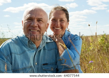 Lovely mature couple poising against summer landscape