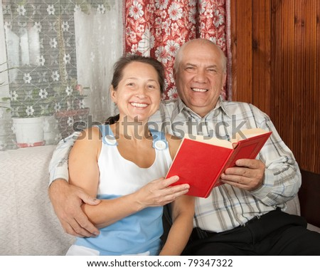 Lovely mature couple reading on sofa at home