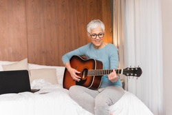 Lovely mature woman playing guitar in her bedroom, Free time and hobbies concept