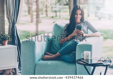 Lovely message from him. Beautiful young smiling woman looking at her smart phone while sitting in a big comfortable chair at home