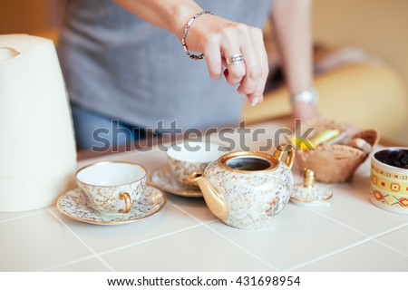 Lovely middle-aged blond woman with a beaming smile sitting at home having tea #431698954