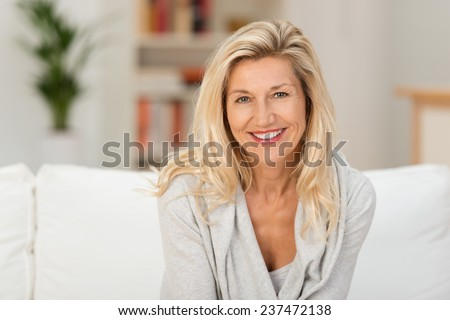 Lovely middle-aged blond woman with a beaming smile sitting on a sofa at home looking at the camera #237472138