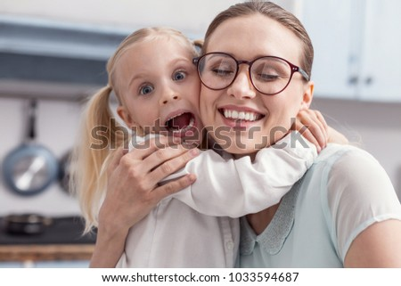 Lovely moment. Loving adorable sincere mother and daughter sharing emotions while girl opening mouth and shouting #1033594687