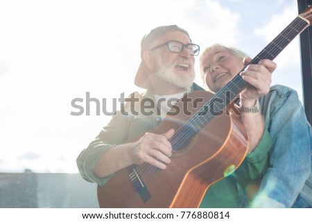Lovely moment. Low angle portrait of mature charming couple sitting at window while husband is performing favorite song on guitar and wife is tenderly hugging him. Copy space #776880814