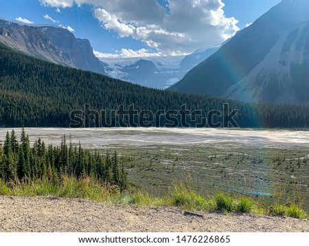 Lovely mountain river with a mountain valley behind, blue sky and fluffy, white clouds.