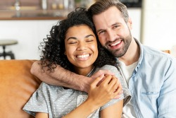 Lovely multiracial couple in embraces in cozy living room at home. A smiling caucasian guy is hugging charming african girl. Love and affection concept