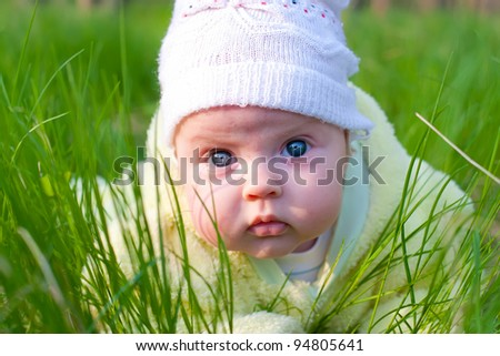 Lovely newborn baby with blue eyes wearing a white cap lying on green grass. Spring vacation.