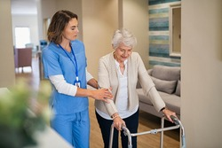 Lovely nurse helping old woman to walk at nursing home with walker. Young nurse helping senior patient using a walking frame to walk in hospital corridor. Caregiver and disabled lady in care facility.