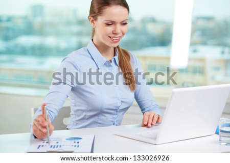 Lovely office girl being satisfied with financial results