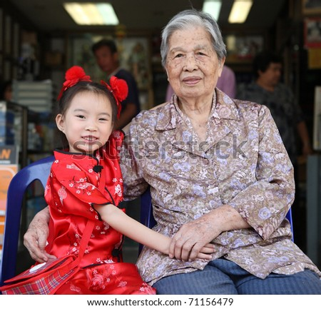 Lovely Old and Kid Asian Chinese woman portrait in home background