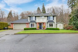 Lovely pale green Colonial home features red brick porch with columns, attached garage, shed and well manicured front yard. Northwest, USA