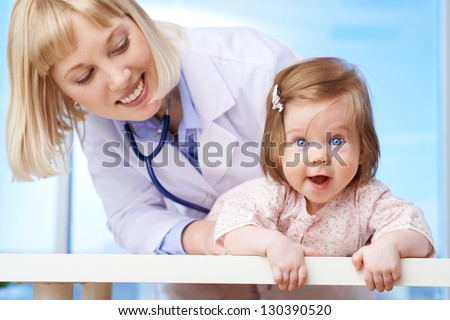Lovely pediatrician taking care of cute baby in hospital - stock photo