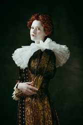 Lovely portrait. Medieval redhead young woman in golden vintage clothing as a duchess standing crossing hands on dark green background. Concept of comparison of eras, modernity and renaissance.