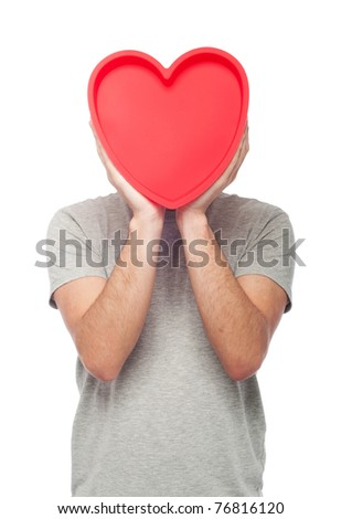 lovely portrait of a young man holding a red heart (isolated on white background)