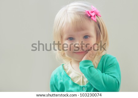 Lovely portrait of smiling baby girl with bow