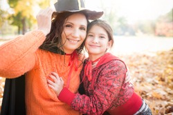 Lovely positive young mother In a paper hat with her smiling little daughter walks in the park among the autumn leaves. Halloween meeting concept