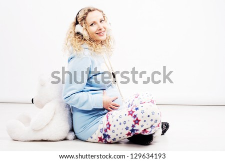 Lovely pregnant woman in pajamas and headphones with teddy bear